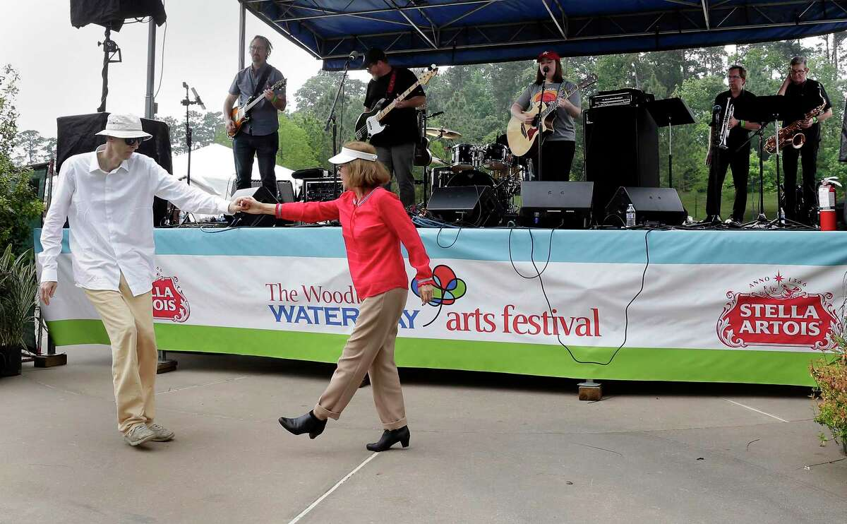 The 2021 version of The Waterway Arts Festival is slated for April 10-11, with the popular Art Dash night of whimsy on Friday, April 9. Here in this archive image, Carl and Lupe Sharrah dance as Mikayla Griffin performs at the Palette Cafe' Stage during The Woodlands Waterway Arts Festival Saturday, Apr. 13, 2019.