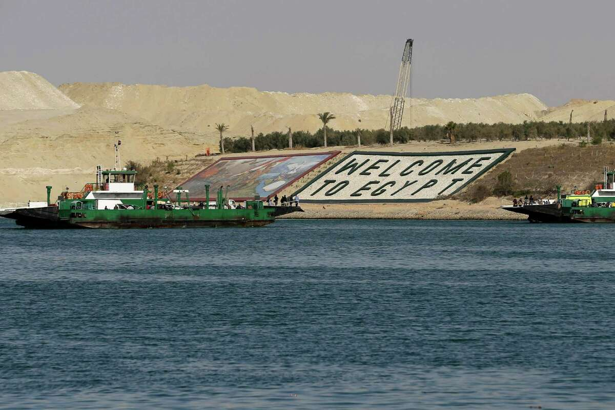 FILE - In this Feb. 4, 2015 file photo, ferries cross the Suez Canal during a media tour in Ismailia, Egypt. Egypt on Thursday, Aug. 6, will unveil a major extension of the Suez Canal, a mega-project that has emerged as a cornerstone of President Abdel-Fattah el-Sissi's efforts to restore national pride and revive the economy after years of unrest. (AP Photo/Hassan Ammar, File)