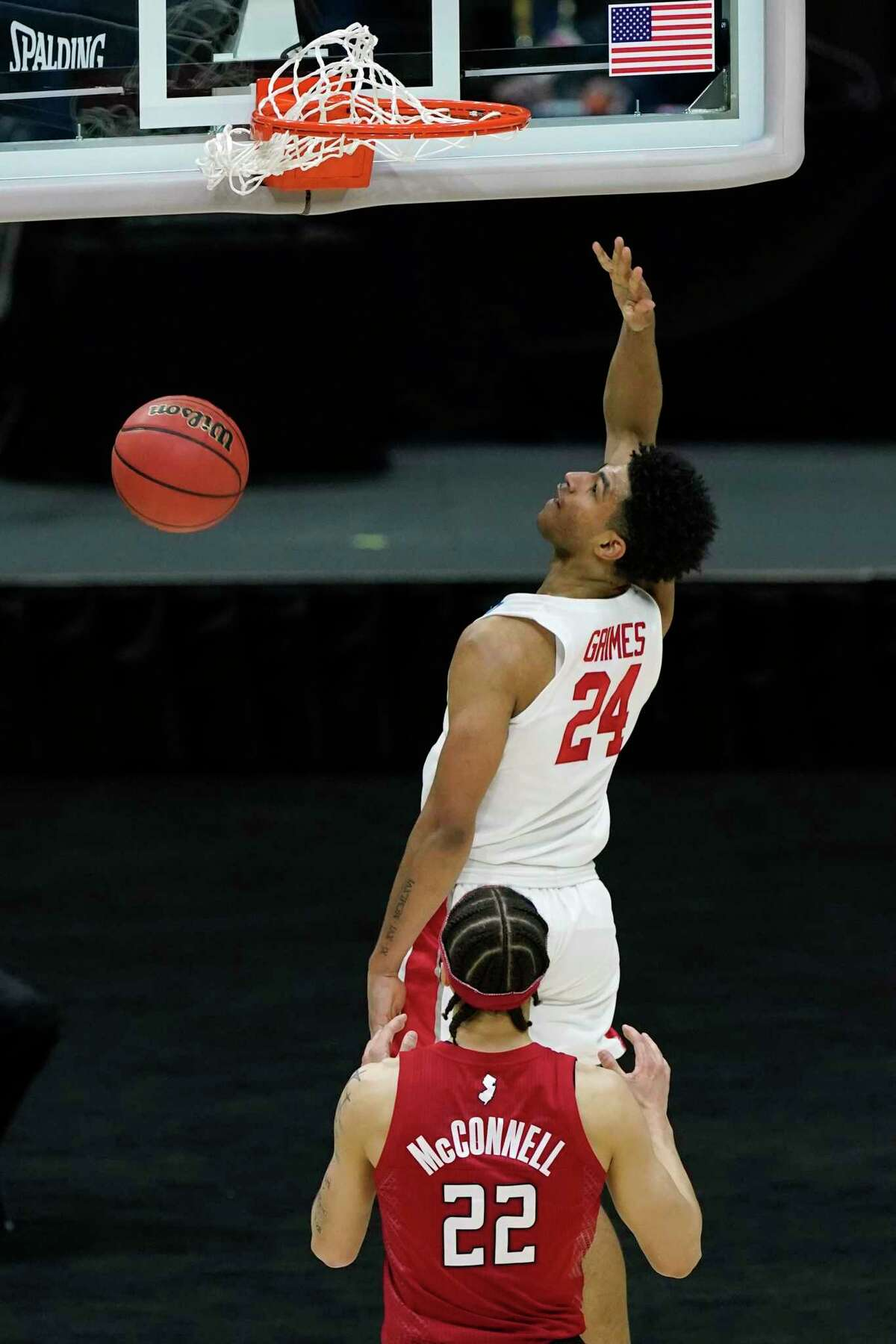 Houston's Quentin Grimes (24) scores ahead of Rutgers' Caleb McConnell (22) during the second half of a college basketball game in the second round of the NCAA tournament at Lucas Oil Stadium in Indianapolis Sunday, March 21, 2021. Grimes scored 22 points as Houston won 63-60. (AP Photo/Mark Humphrey)