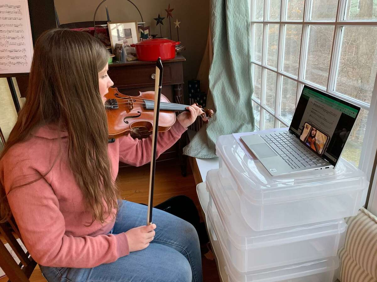 A Ridgefield High School student guides her fifth-grade violin mentee through a lesson over FaceTime.