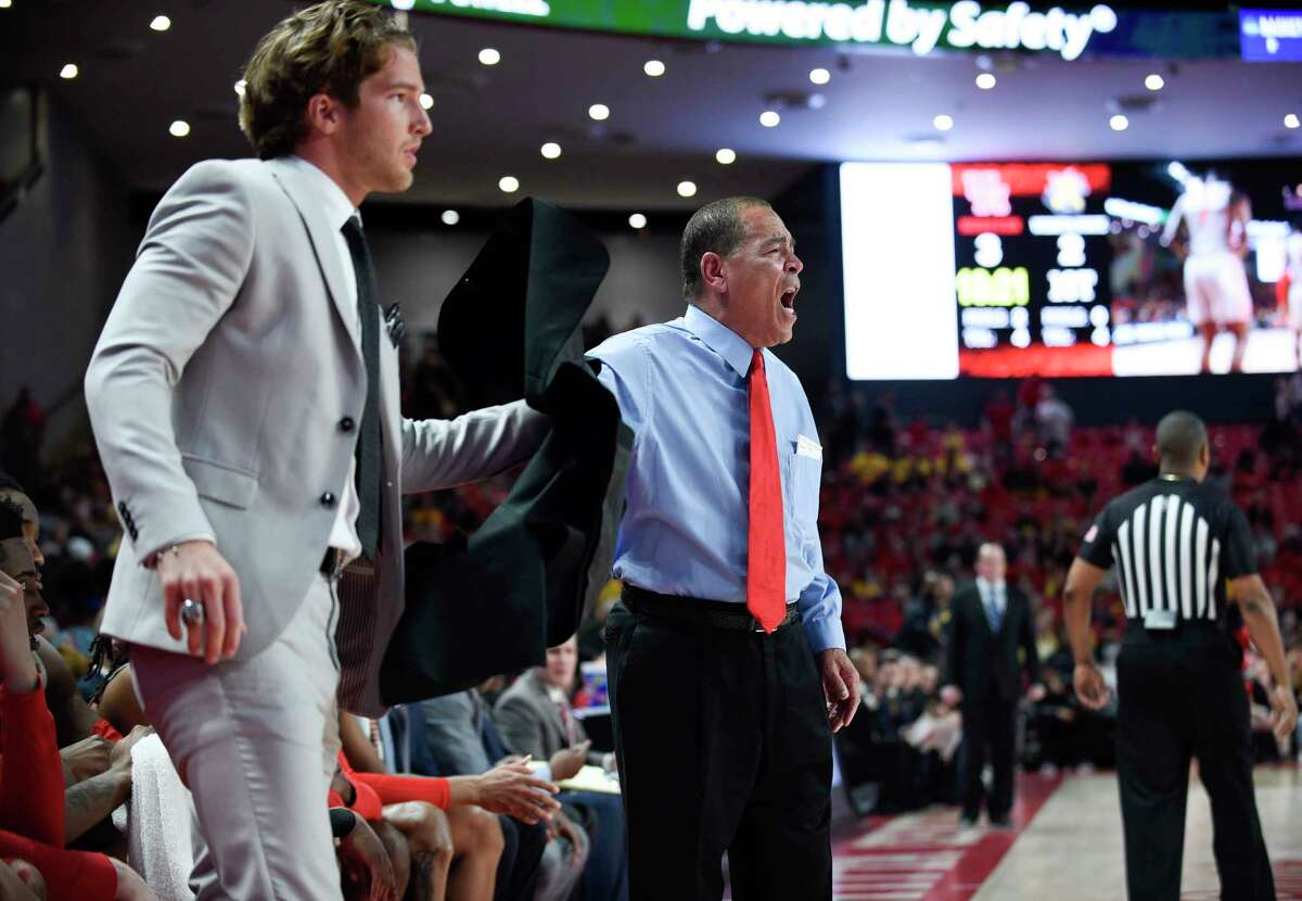 Houston head coach Kelvin Sampson, right, hands his jacket to graduate assistant Landon Goesling during the first half of an NCAA college basketball game against Wichita State, Sunday, Feb. 9, 2020, in Houston.