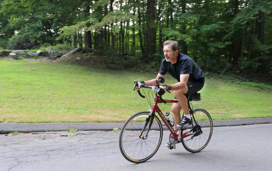 Stephen Szurlej rides his bike past the site on Long Ridge Road in Danbury where Bethel is proposing to build a 750,000-gallon water tank. Szurlej, who lives across the street from the property, says it will ruin the aesthetics of the scenic roadway. Photo: File Photo / The News-Times File Photo
