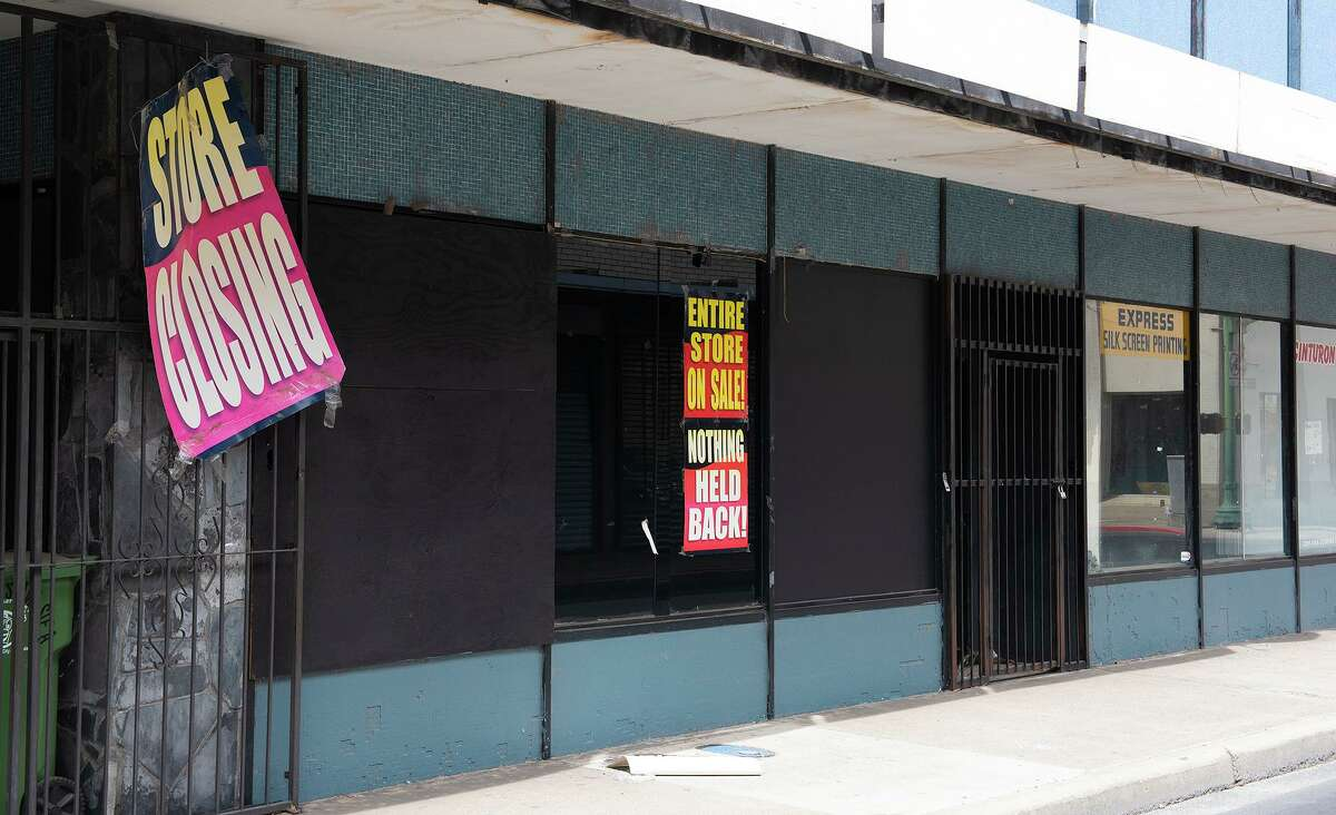 A store closing sign hangs off the gate of a closed down business, Tuesday, March 23, 2021, in downtown Laredo.