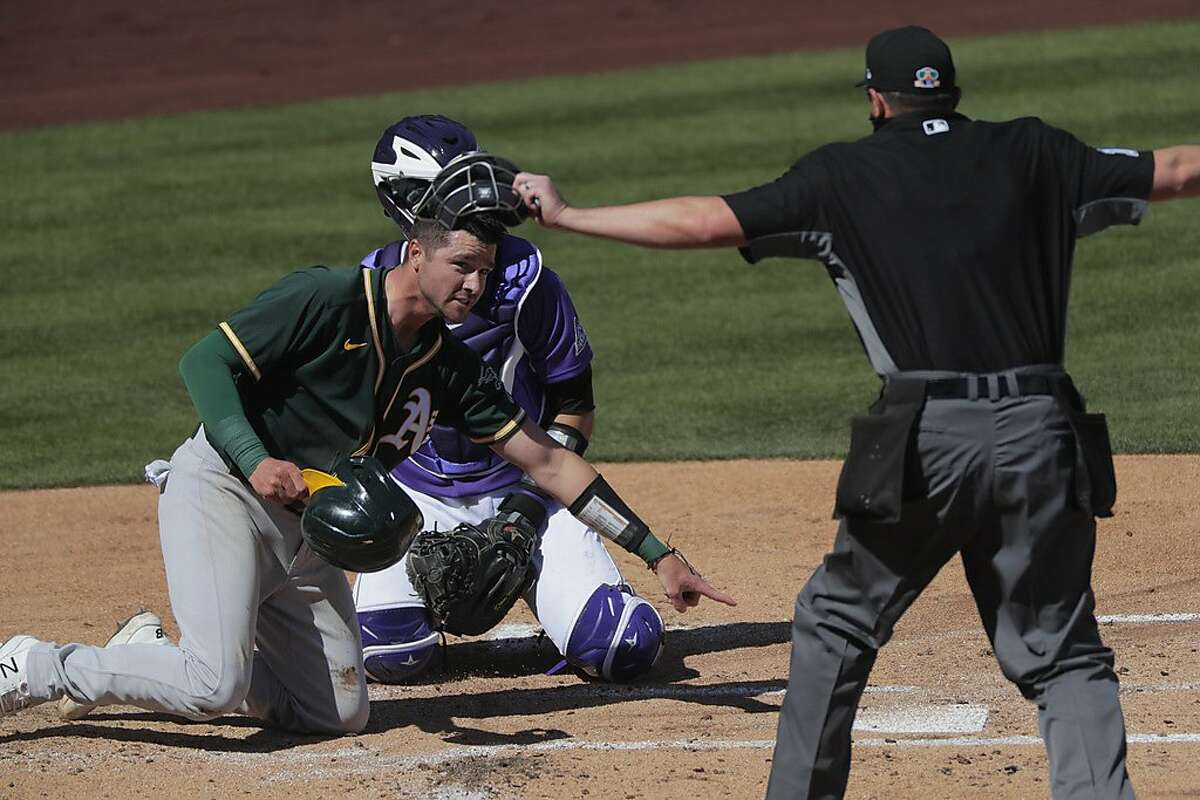 Austin Allen (30) safe at home on a hit by Pete Kozma (38) in the second inning as the Oakland Athletics played the Colorado Rockies in a spring training game at Salt River Fields at Talking Stick Park in Scottsdale, Ariz., on Wednesday, March 3, 2021