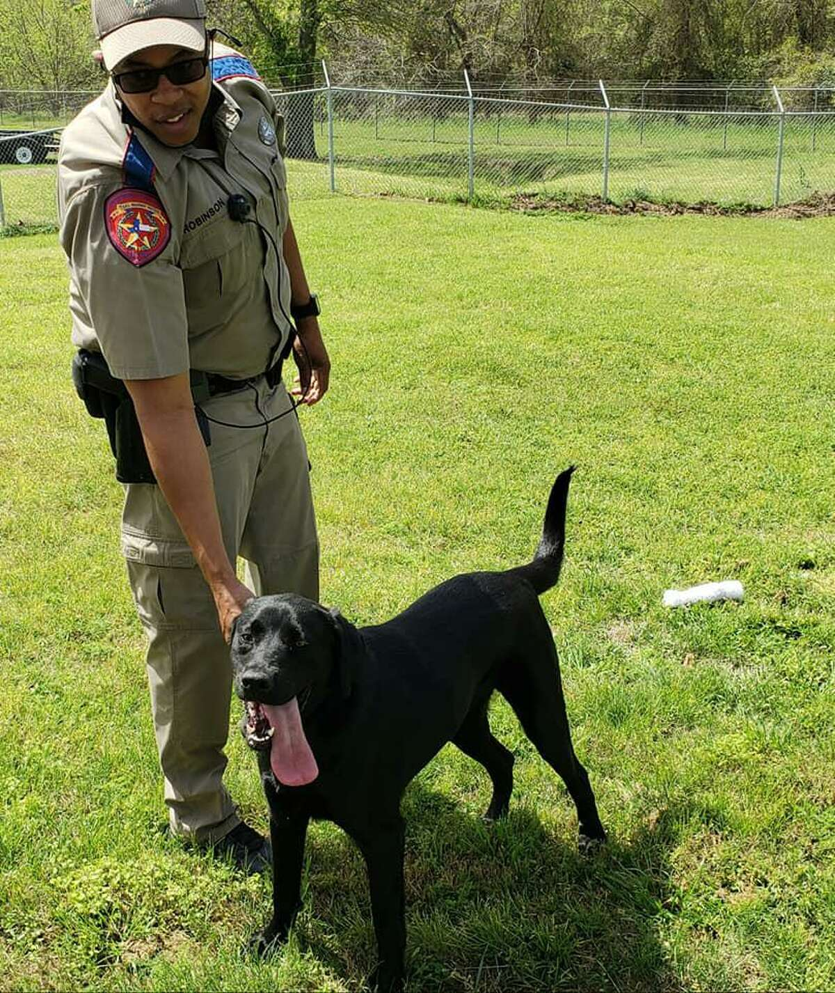 State trooper Corey Robinson plays with Dog, a former stray that might become a K-9 cop on March 23, 2021.