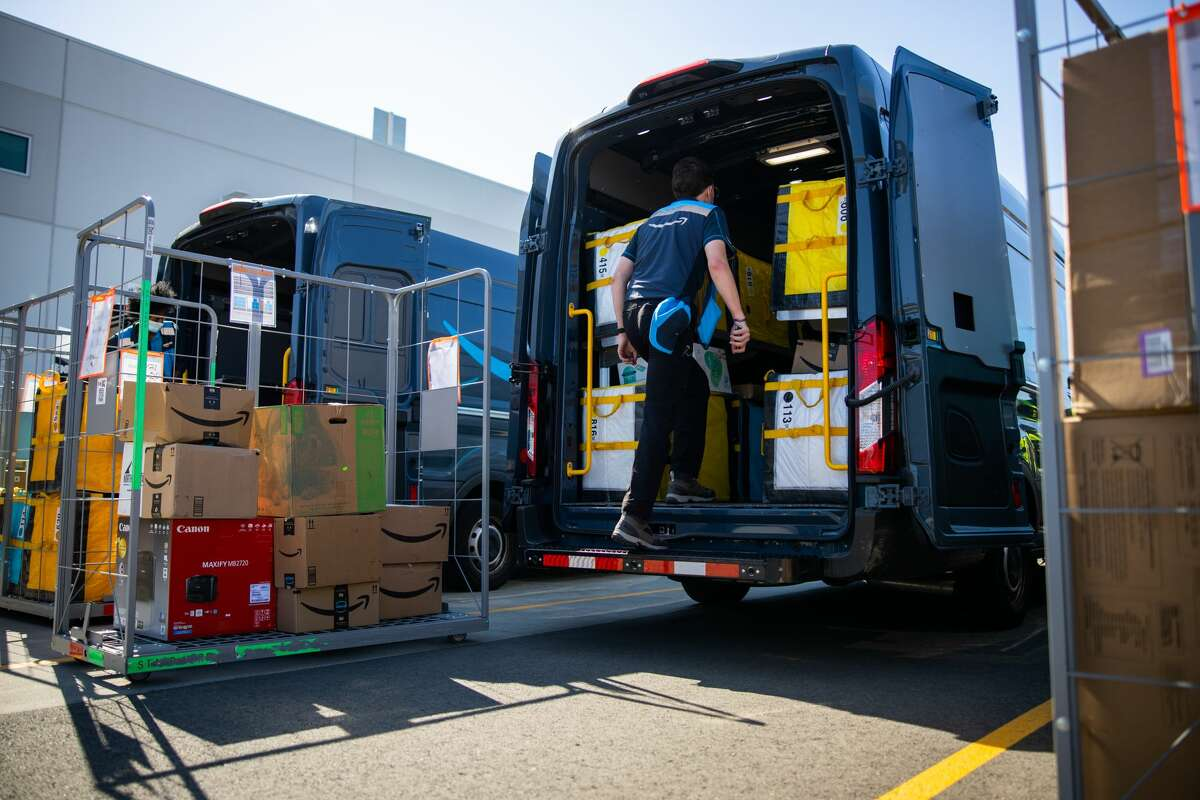 A delivery driver loads a van at an Amazon facility.