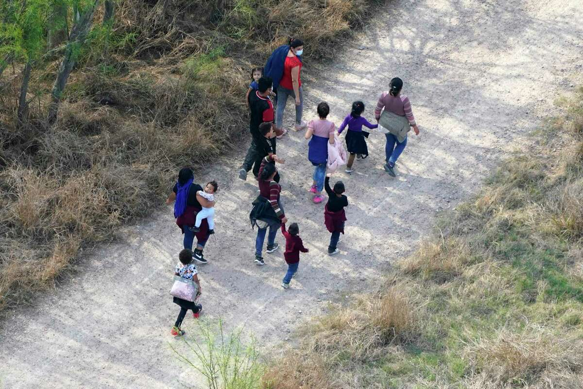 Migrants walk on a dirt road after crossing the U.S.-Mexico border on March 23, 2021, in Mission, Texas. The number of migrants at the Southwest border has swelled in recent weeks.