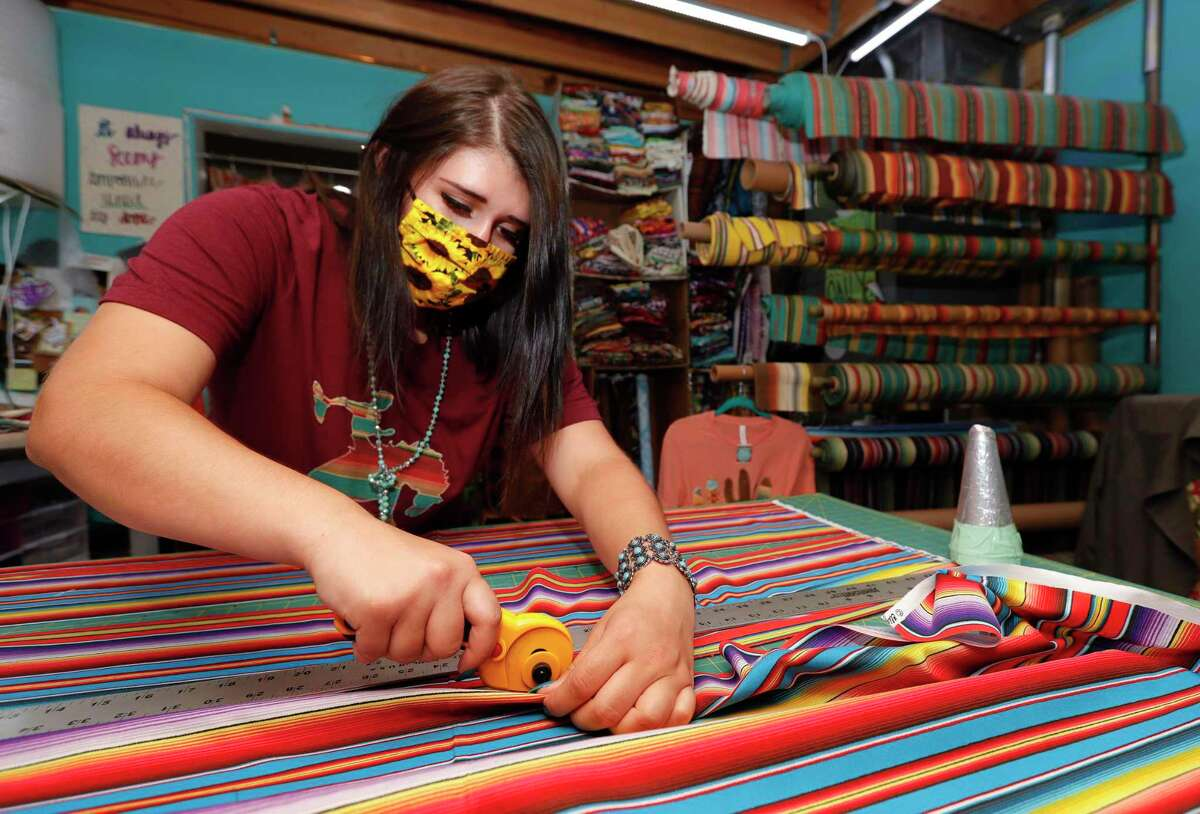 Andrea Kienholz cuts fabric for face masks at Sweet Texas Treasures Boutique, Friday, July 3, 2020, in Montgomery.