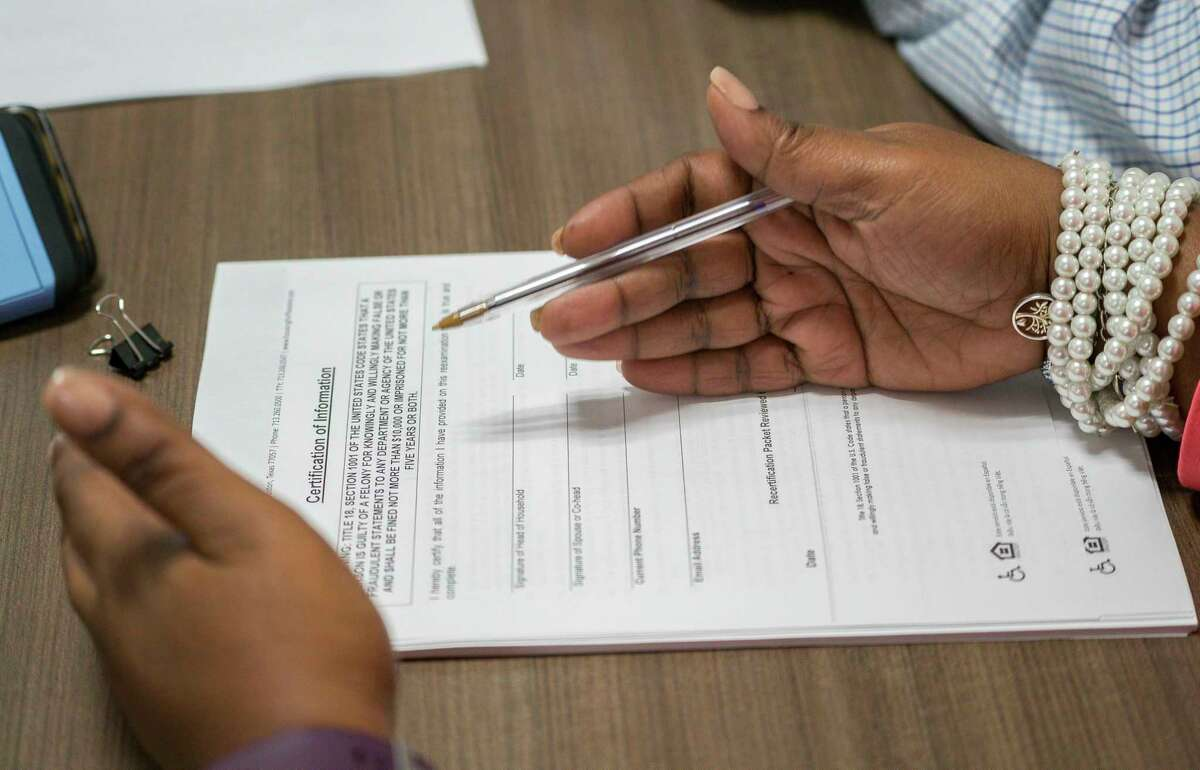Housing program coordinator Joanquinta White, at the Hay Center in Houston, reviews a housing voucher application with Alec Chester, 20, Thursday, March 7, 2019.