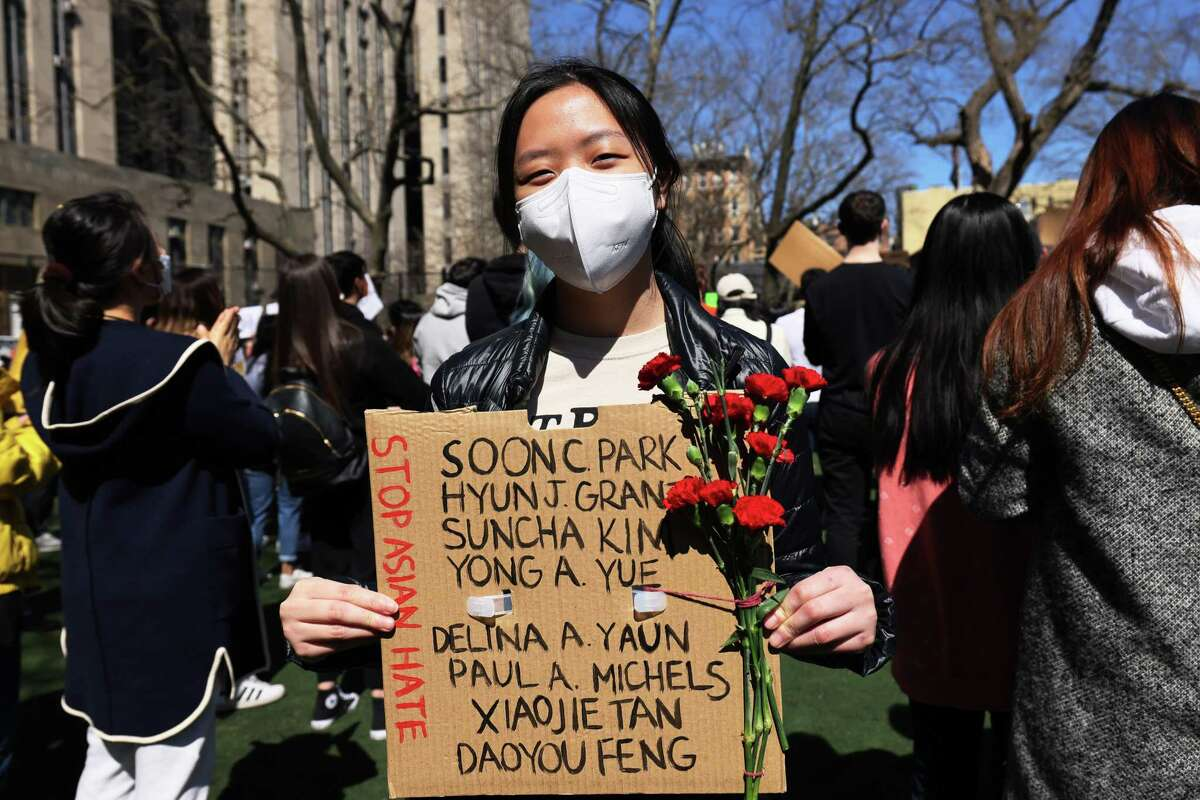 NEW YORK, NEW YORK - MARCH 21: Amy Zhao holds up a sign and flowers at a rally against hate in Columbus Park on March 21, 2021 in the Chinatown neighborhood of Manhattan in New York, New York. A rally for solidarity was organized in response to a rise in hate crimes against the Asian community since the start of the coronavirus (COVID-19) pandemic in 2020. On March 16 in Atlanta, Georgia, a man went on a shooting spree in three spas that left eight people dead, including six Asian women. (Photo by Michael M. Santiago/Getty Images)