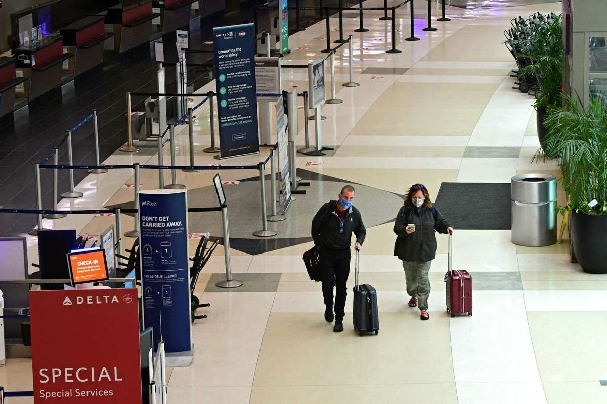 Passengers are seen walking through the terminal at the Albany International Airport on Wednesday, March 24, 2021 in Colonie, N.Y. Airport boardings are climbing as more people get vaccinated. (Lori Van Buren/Times Union)