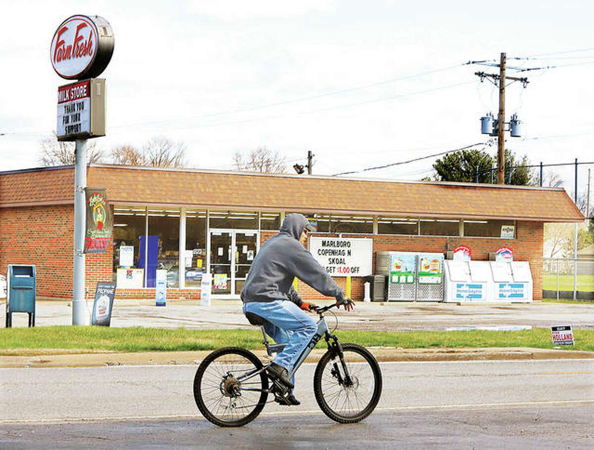 A man on a bicycle on Airline Drive in Rosewood Heights Wednesday pedals past the Farm Fresh store which is seeking re-zoning to allow them to sell packaged liquor inside the store.