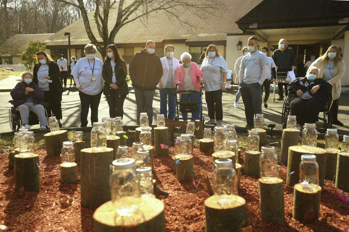 Staff and residents view the memorial in honor of the fifty residents to die since the start of the Covid-19 pandemic one year ago outside Apple Rehab Shelton Lakes in Shelton, Conn. on Tuesday, March 23, 2021. Nearly half of the deaths were due to Covid.
