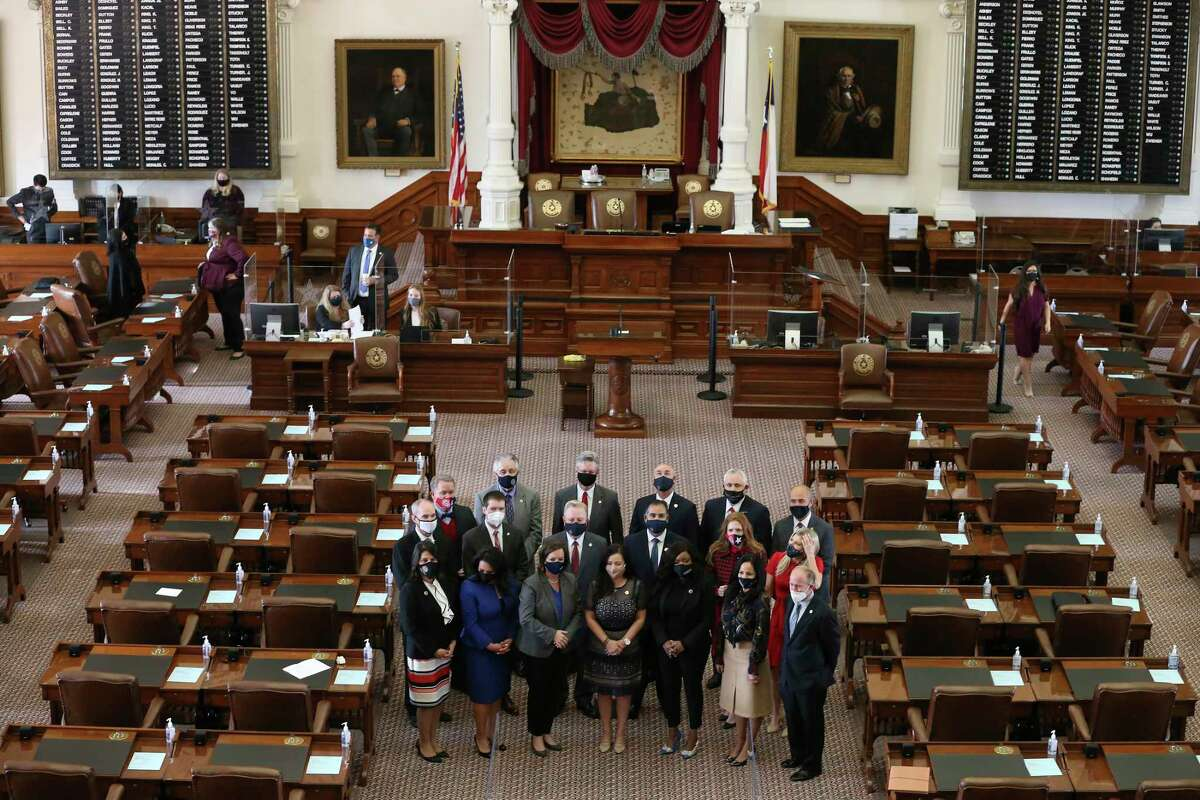 New members of the Texas House of Representatives, some elected in special elections, pose for their pictures in the chamber prior to reconvening, Tuesday, Feb. 9, 2021.