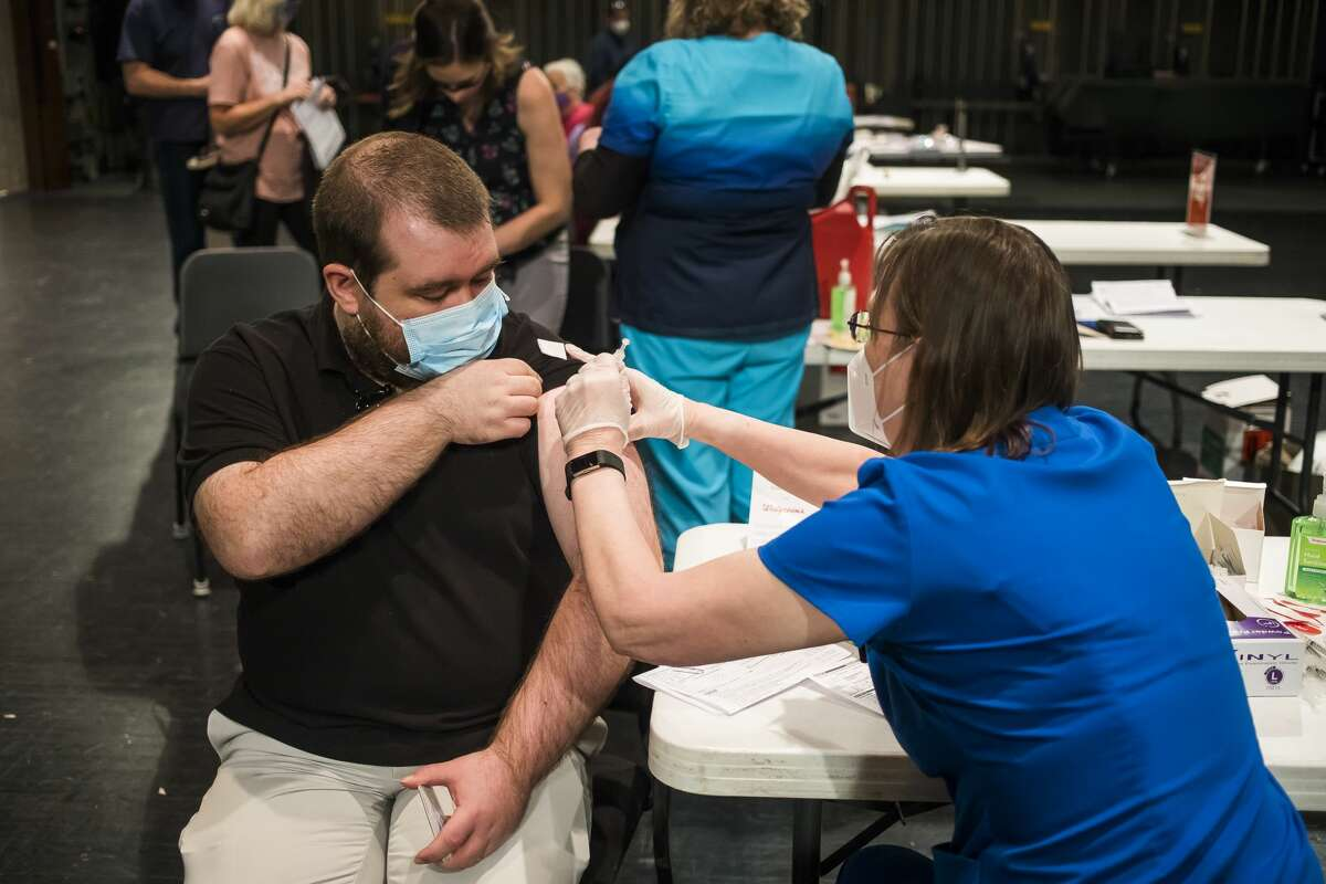 FILE - Hundreds of people receive the Pfizer COVID-19 vaccine during a clinic held in partnership with Walgreens on March 24, 2021 at the Midland Center for the Arts.