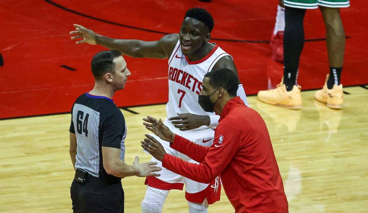 Houston Rockets guard Victor Oladipo (7) and head coach Stephen Silas talk with an official during the second quarter of an NBA basketball game in Houston Sunday, March 14, 2021. (Troy Taormina/Pool Photo via AP)