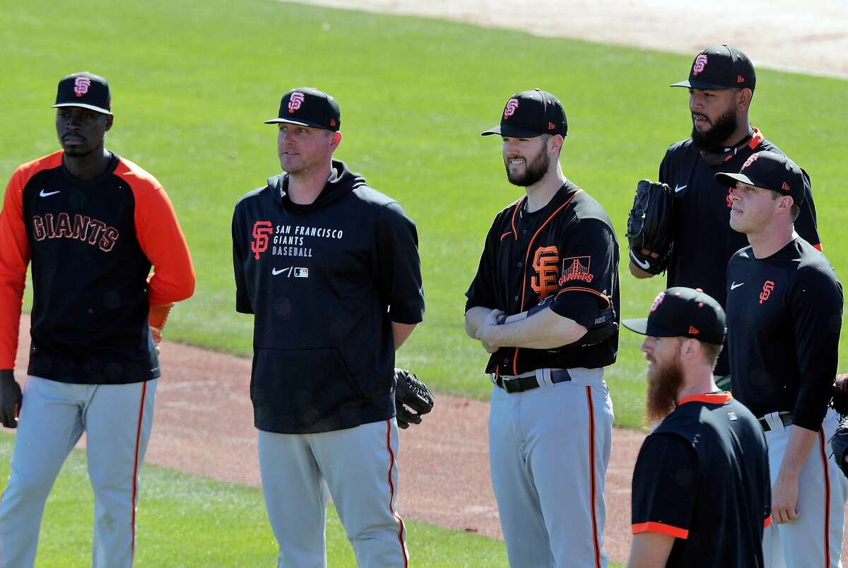 Pitchers, Alex Wood (57), and Jake McGee (17), center, were former Dodgers teammates and now on the practice field as the San Francisco Giants worked out at Scottsdale Stadium in Scottsdale, Ariz., on Monday, March 1, 2021.