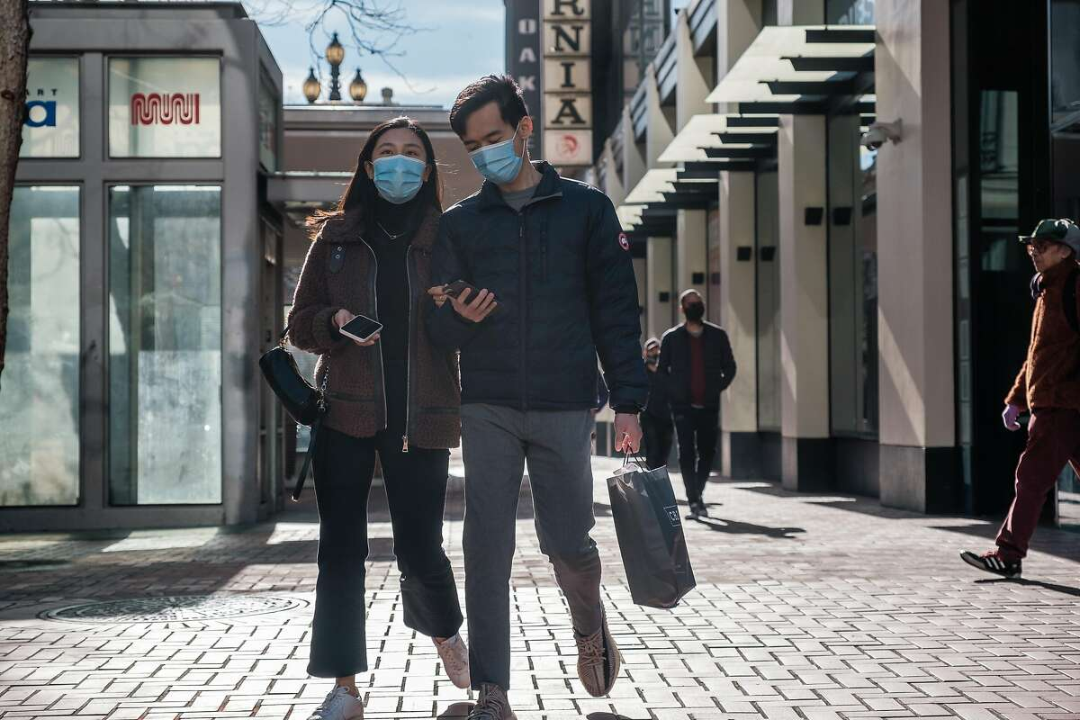 Pedestrians wearing single face masks walk along the sidewalk in San Francisco on Friday, February 12, 2021. The CDC recently said wearing double masks can help protect against the spread of COVID-19.