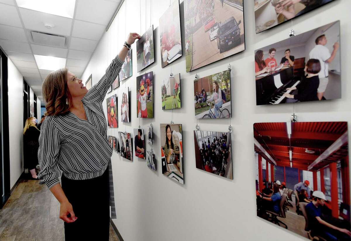 Tracie Craig, Director of the Welcome Center, straightens a hanging collage of campus photographs as she gives a media tour of Lamar University's newest building, which opened this month. Photo made Wednesday, March 24, 2021 Kim Brent/The Enterprise