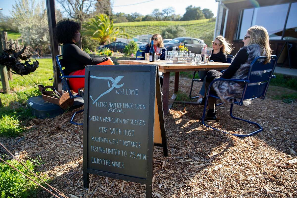 A sign with Covid-19 safety guidelines is placed at each wine tasting station at Matthiasson Winery in Napa, Calif. on Saturday, March 13, 2021.