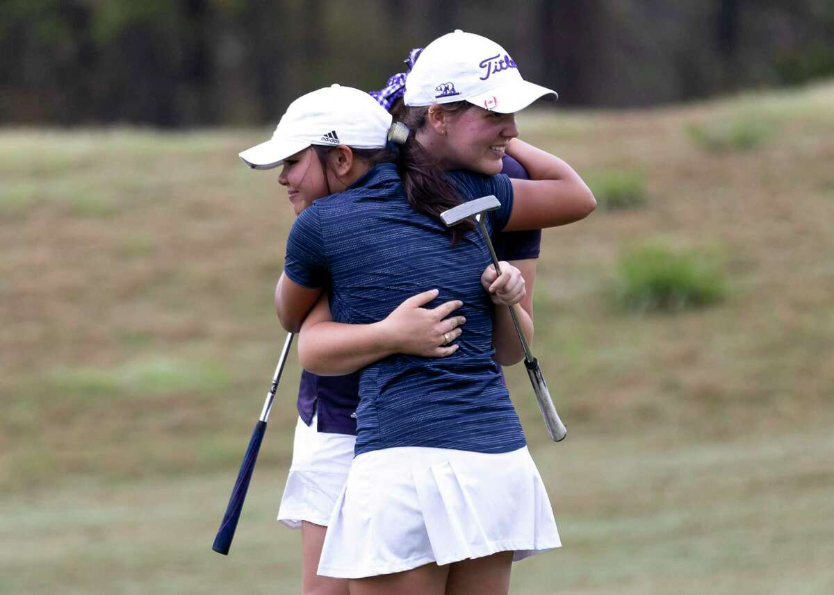 Hannah Nicholson of Montgomery embraces Kailana Davis of Lake Creek after Nicholson secured the second regional spot during the District 20-5A girls golf championship at Lake Windcrest Golf Club, Wednesday, March 24, 2021, in Magnolia.