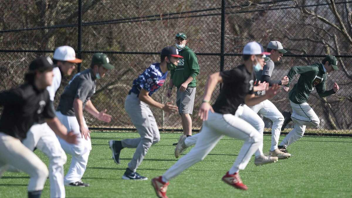 Norwalk baseball coach Ryan Mitchell watches from a distance as the Bears run sprints during the first week of pitchers and catchers for the baseball preseason at the Nathan Hale Middle School field on Tuesday, March 23, 2021.