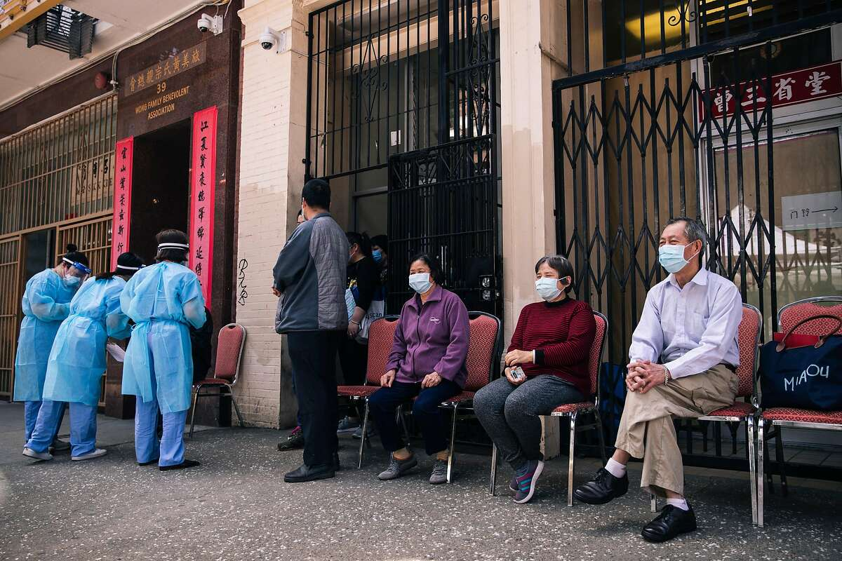 Residents from Hoy Sun Ning Yung Benevolent Association on Chinatown's Waverly Place waits to be tested for the COVID-19 coronavirus disease during a joint pilot program between the Chinese Hospital and the San Francisco Department of Public Health in San Francisco, Calif. on Friday, May 22, 2020.