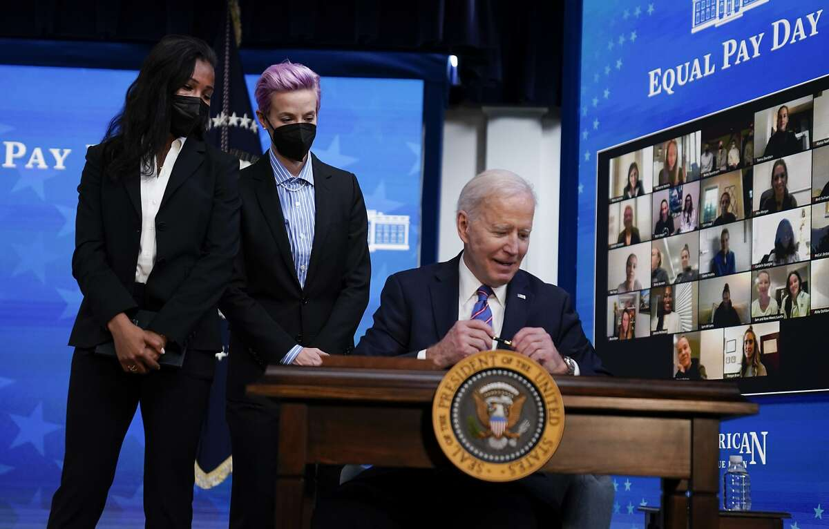 President Biden signs a proclamation recognizing Equal Pay Day as U.S. Soccer's Margaret Purce and Megan Rapinoe watch.