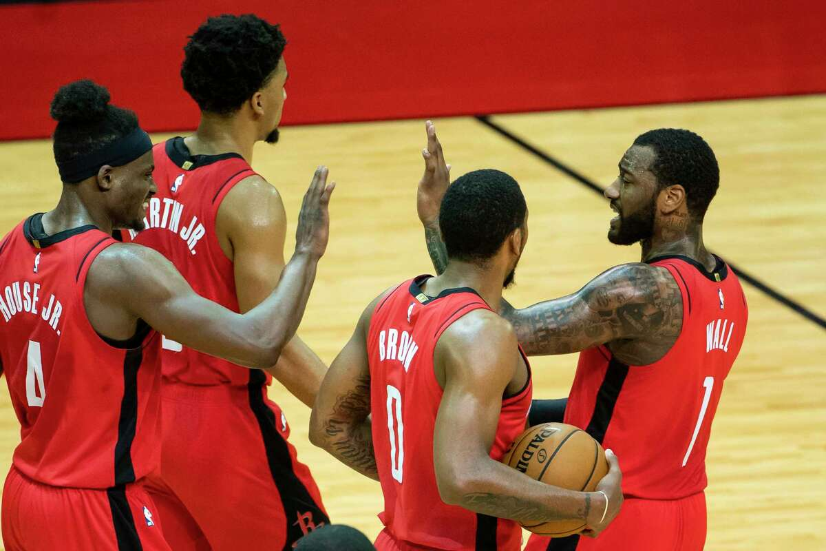 Houston Rockets guard John Wall (1) high-fives his teammates at the end of the second quarter of an NBA game between the Houston Rockets and Charlotte Hornets on Wednesday, March 24, 2021, at Toyota Center in Houston.