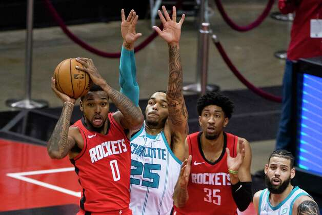 Houston Rockets forward Sterling Brown (0) passes the ball back out defended by Charlotte Hornets forward P.J. Washington (25) during the second quarter of an NBA game between the Houston Rockets and Charlotte Hornets on Wednesday, March 24, 2021, at Toyota Center in Houston. Photo: Mark Mulligan, Staff Photographer / © 2021 Mark Mulligan / Houston Chronicle