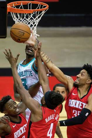 Houston Rockets forward Jae'Sean Tate (8), forward Danuel House Jr. (4) and center Christian Wood (35) try to grab a rebound from Charlotte Hornets center Bismack Biyombo (8) during the second quarter of an NBA game between the Houston Rockets and Charlotte Hornets on Wednesday, March 24, 2021, at Toyota Center in Houston. Photo: Mark Mulligan, Staff Photographer / © 2021 Mark Mulligan / Houston Chronicle