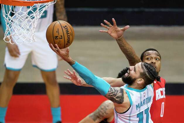Charlotte Hornets forward Cody Martin (11) shoots around Houston Rockets forward Sterling Brown (0) during the first quarter of an NBA game between the Houston Rockets and Charlotte Hornets on Wednesday, March 24, 2021, at Toyota Center in Houston. Photo: Mark Mulligan, Staff Photographer / © 2021 Mark Mulligan / Houston Chronicle