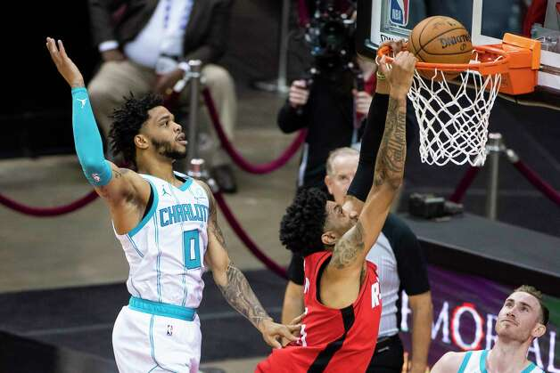 Houston Rockets center Christian Wood (35) dunks as he is defended by Charlotte Hornets forward Miles Bridges (0) during the first quarter of an NBA game between the Houston Rockets and Charlotte Hornets on Wednesday, March 24, 2021, at Toyota Center in Houston. Photo: Mark Mulligan, Staff Photographer / © 2021 Mark Mulligan / Houston Chronicle