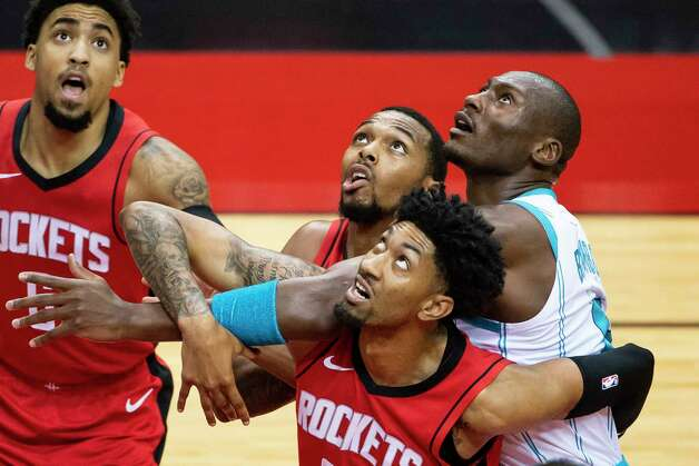 Houston Rockets forward Sterling Brown (0), Houston Rockets center Christian Wood (35) and Charlotte Hornets center Bismack Biyombo (8) battle for a rebound during the first quarter of an NBA game between the Houston Rockets and Charlotte Hornets on Wednesday, March 24, 2021, at Toyota Center in Houston. Photo: Mark Mulligan, Staff Photographer / © 2021 Mark Mulligan / Houston Chronicle