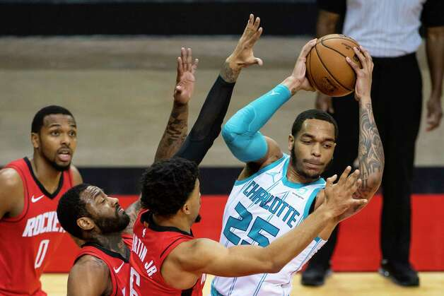 Charlotte Hornets forward P.J. Washington (25) is defended by Houston Rockets forward Kenyon Martin Jr. (6) and Houston Rockets guard John Wall (1) during the first quarter of an NBA game between the Houston Rockets and Charlotte Hornets on Wednesday, March 24, 2021, at Toyota Center in Houston. Photo: Mark Mulligan, Staff Photographer / © 2021 Mark Mulligan / Houston Chronicle