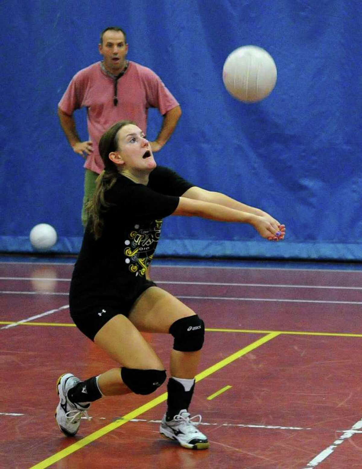 As Coach Jon Shepro looks on, Melissa Sweeney bumps the ball, during volleyball practice at Staples High in Westport, Conn. on Thursday September 2, 2010.