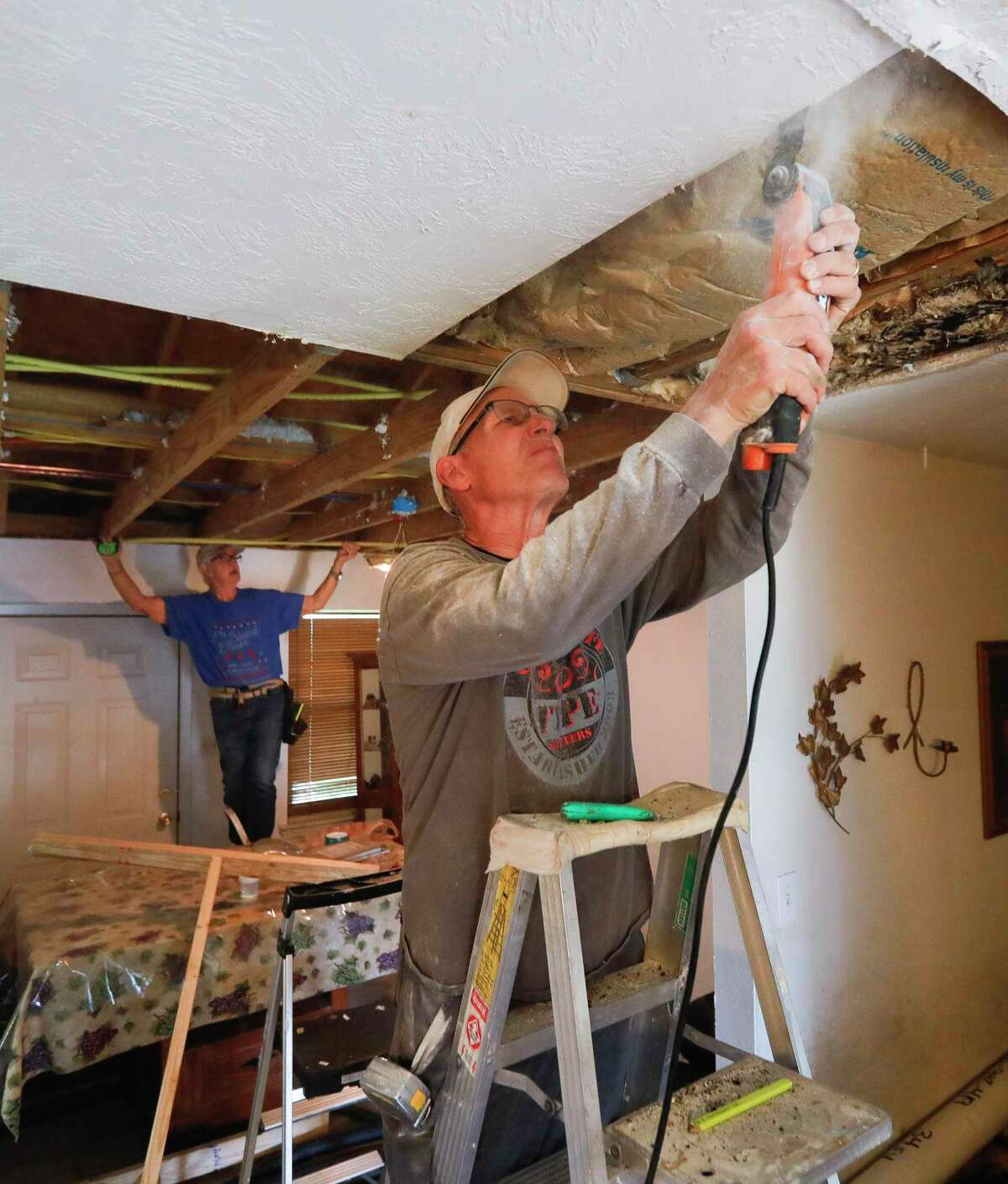"""Allan Schneider, left, cuts drywall as Jerry Neuberger measures a wall while helping repair Delia Brown's water-damaged home from February's arctic blast, Tuesday, March 23, 2021, in Conroe. 'They've been such a blessing to me,"""" Brown said. """"I don't know what I would have done without them."""" Schneider and Neuberger are part of The Woodlands Methodist Church's 60-member 'Geezer Group,' a group of volunteers help those in need with small construction projects usually after natural disasters."""