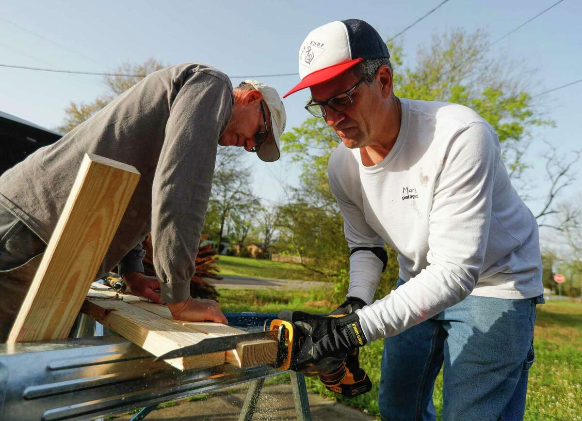 """Mark Langenberg, right, cuts a section off a board as Allan Schneider holds it down while helping repair Delia Brown's water-damaged home from February's arctic blast, Tuesday, March 23, 2021, in Conroe. 'They've been such a blessing to me,"""" Brown said. """"I don't know what I would have done without them."""" Langenberg and Schneider are part of The Woodlands Methodist Church's 60-member 'Geezer Group,' a group of volunteers help those in need with small construction projects usually after natural disasters."""