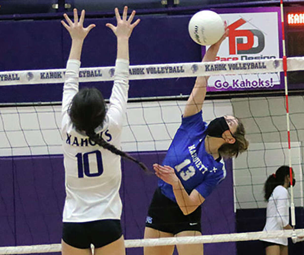 Marquette Catholic's Kristine Lauritzen hits past the block of Collinsville's Lexi Biciocchi (10) in a March 17 match at Collinsville. On Wednesday, Lauritzen had four kills in the Explorers' loss at Freeburg.