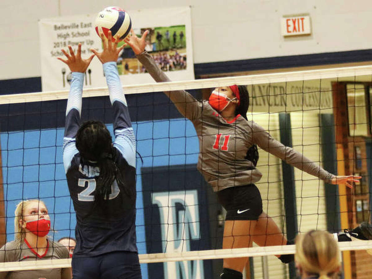 Alton's Renee Raglin (right), shown tipping over Belleville East's Mariah May during a March 16 match in Belleville, had two kills and two blocks Wednesday in the Redbirds' SWC loss to O'Fallon.