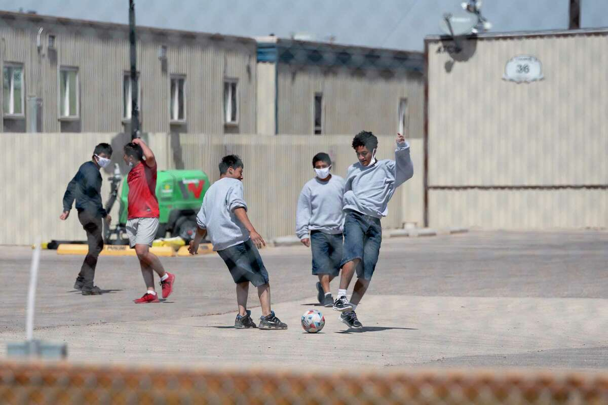 Migrant teenagers play soccer behind the fence of a temporary holding facility for migrant minors from the southern border of the United States, Wednesday, March 24, 2021, south of Midland, Texas. (Odessa American/Odessa American via AP)