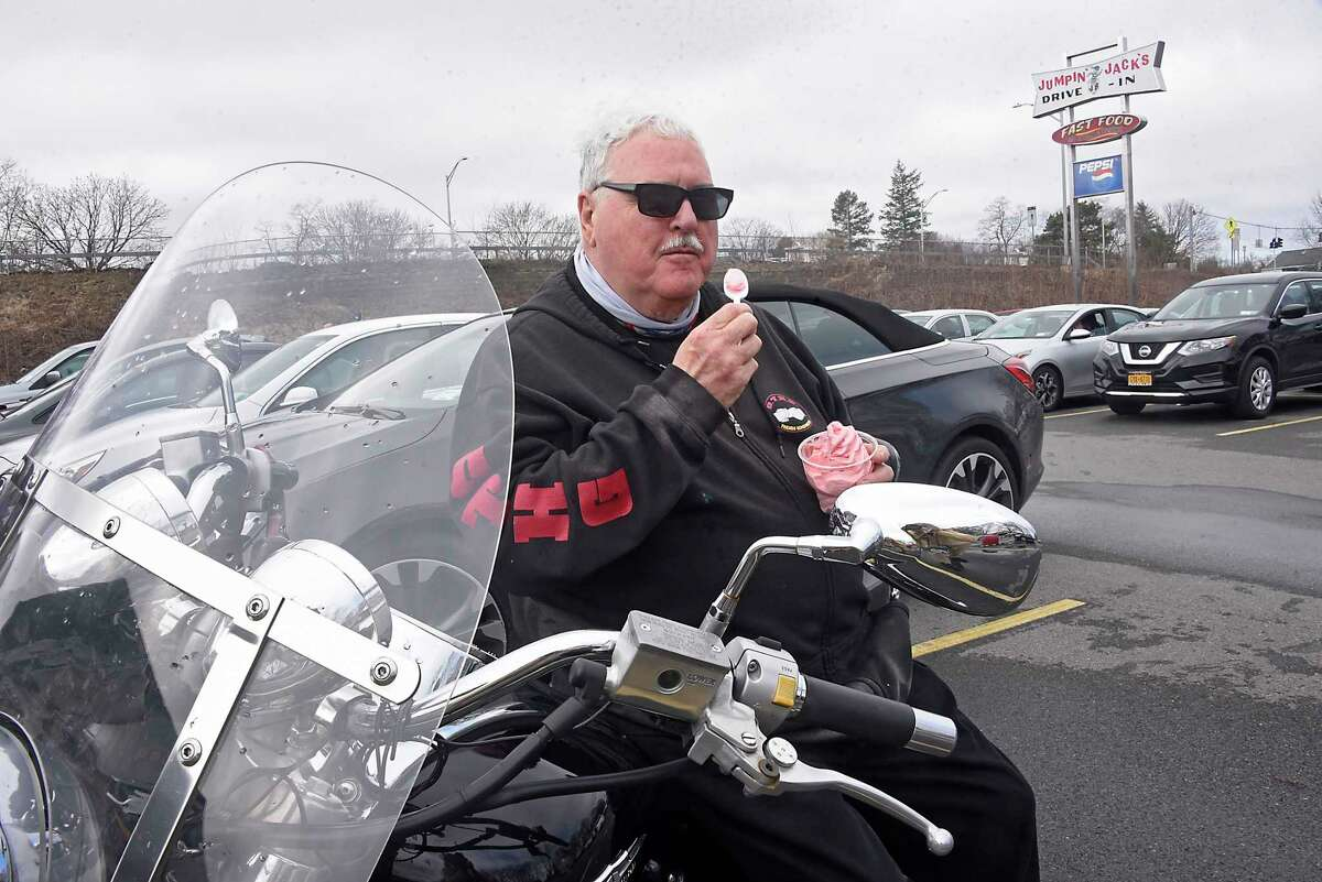 Patrick Bailey of Schenectady enjoys a strawberry yogurt soft serve while sitting on his motorcycle at Jumpin' Jack's Drive-In on Thursday, March 25, 2021 in Scotia, N.Y. Today was opening day of the season for the local favorite hamburger and ice cream spot. (Lori Van Buren/Times Union)