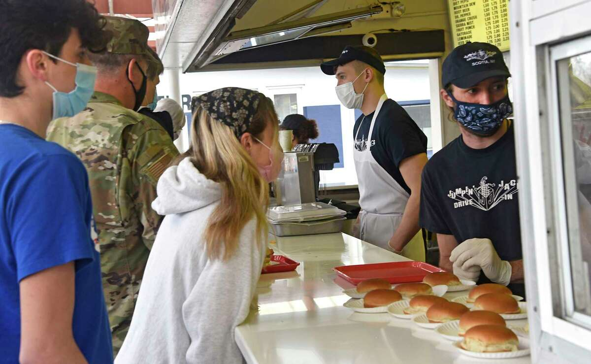 An employee turns his ear toward a customer to hear her order through her face mask at Jumpin' Jack's Drive-In as the local favorite hamburger and ice cream spot opens for the season on Thursday, March 25, 2021 in Scotia, N.Y. (Lori Van Buren/Times Union)