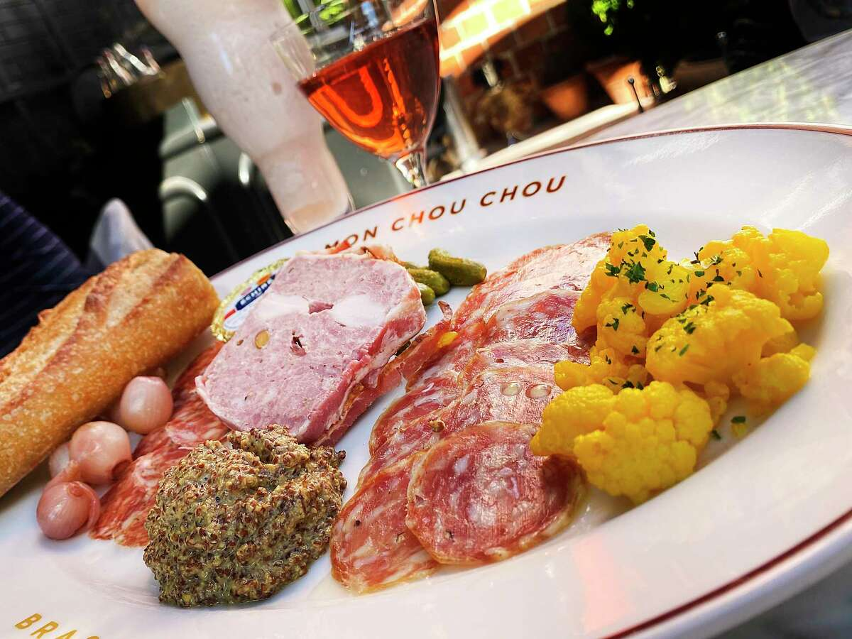 A housemade charcuterie sampler includes, from left, saucisson rouge, country paté with pork, rabbit loin and pistachios wrapped in bacon and a sausage called rosette de Lyon, along with pickled onions, cornichons, moutarde de Meaux and pickled cauliflower at Brasserie Mon Chou Chou.