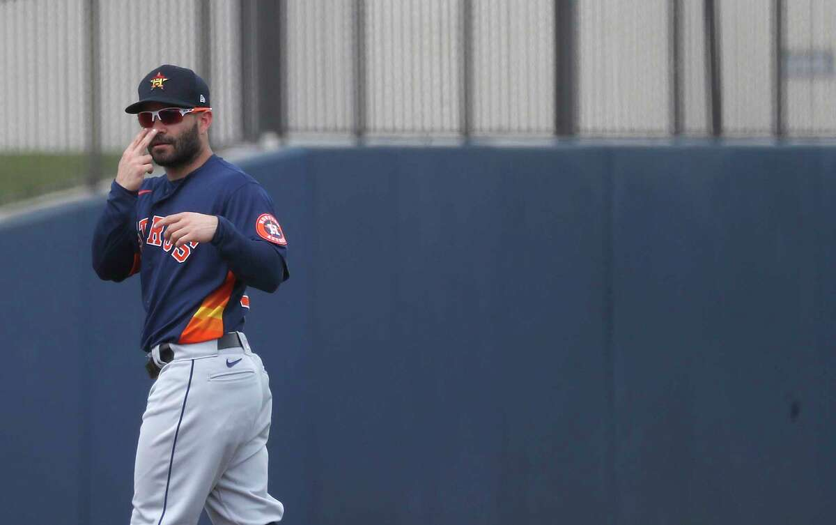 Houston Astros second baseman Jose Altuve (27) signals someone in the Washington Nationals dugout before the start of the first inning of an MLB spring training game at Ballpark of the Palm Beaches in West Palm Beach, Florida, Monday, March 1, 2021.