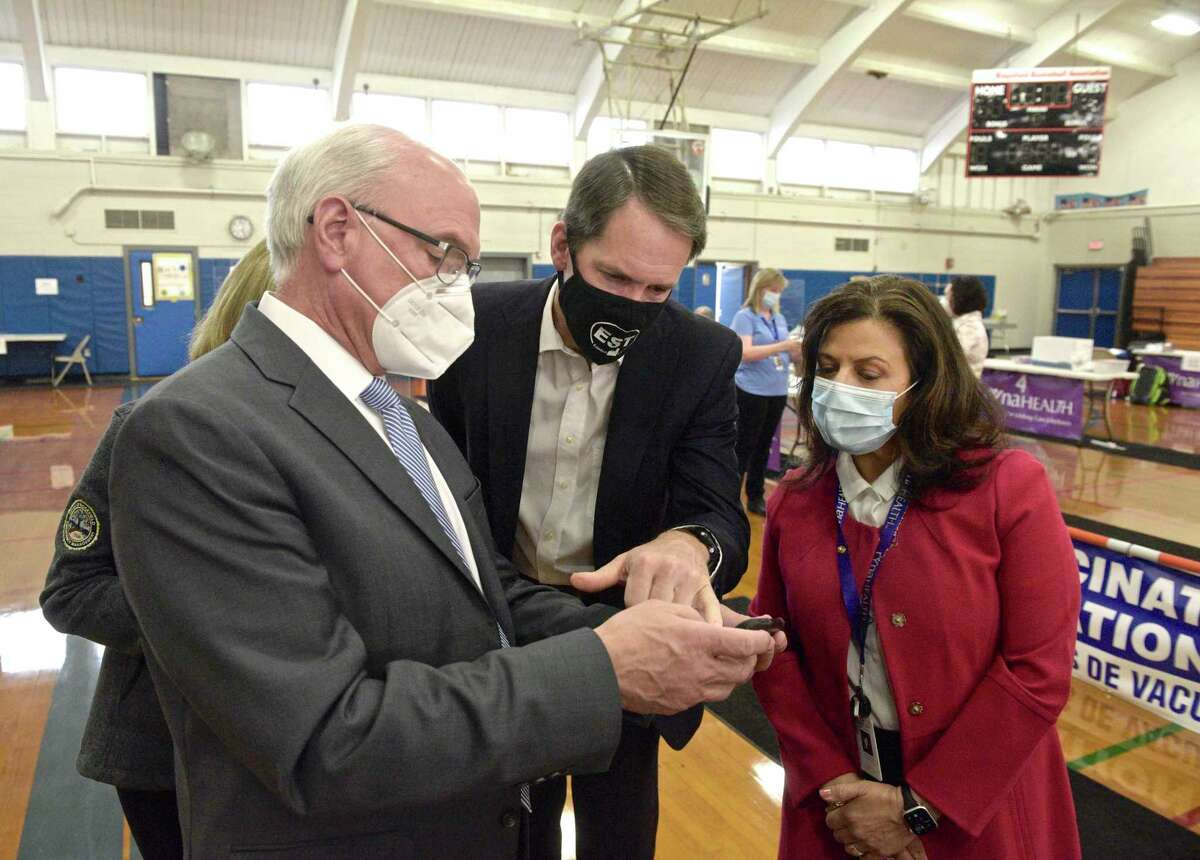 First Selectman Rudy Marconi, left, shows U.S. Representative Jim Himes, center, and Theresa Santoro, President and CEO of RVNA Health, right, COVID data he gets from a retired data scientist from Ridgefield, during a visit to the Yanity Gym vaccination clinic on March 25.