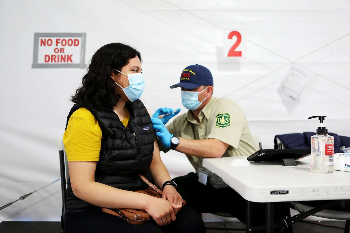 Jessica Avila, 23, of Berkeley, receives her second dose of the Pfizer vaccine as it's administered by Brandon Tatlow, of the U.S. Forest Service, Lassen National Forest, at the Oakland Coliseum vaccination site on Thursday, March 25, 2021, in Oakland, Calif. The Coliseum vaccination site is only scheduled to be open for eight weeks, which means it will close in three weeks unless a deal is reached with local officials.
