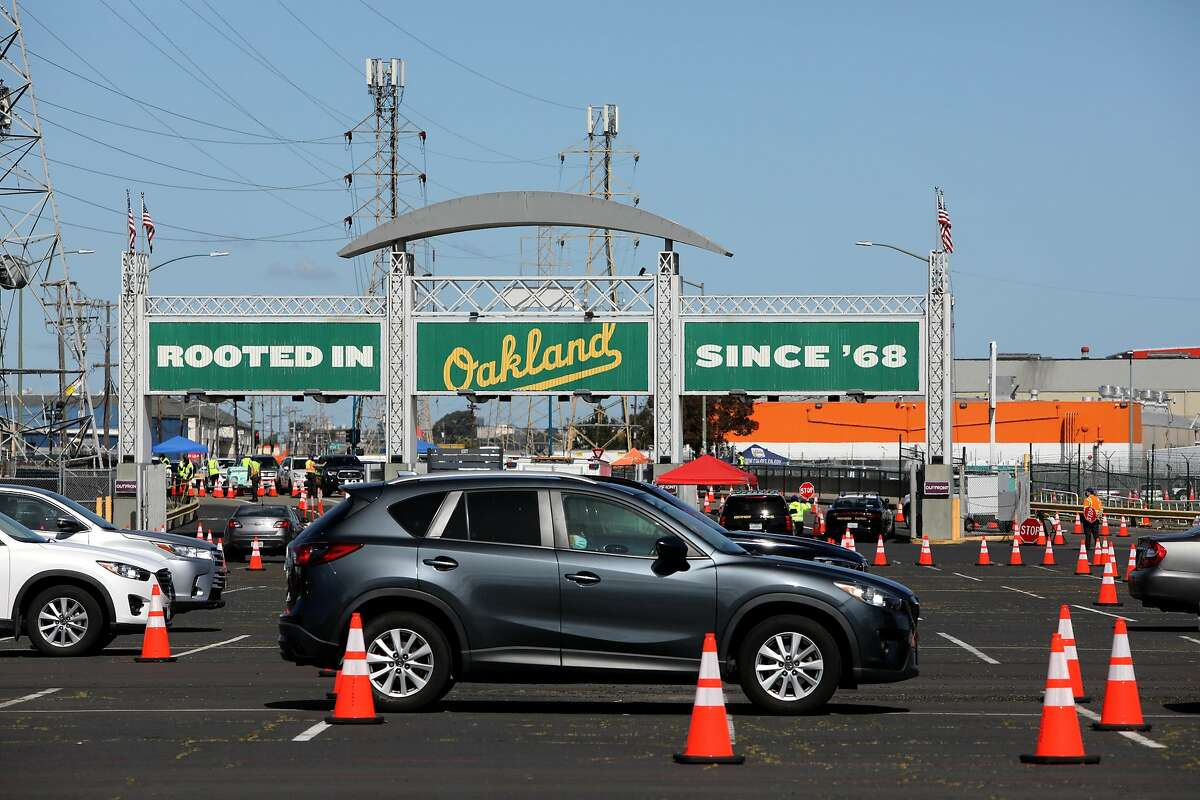 Vehicles wait in line in observation lanes at the Oakland Coliseum vaccination site on Thursday, March 25, 2021, in Oakland, Calif. The Coliseum vaccination site is only scheduled to be open for eight weeks, which means it will close in three weeks unless a deal is reached with local officials.
