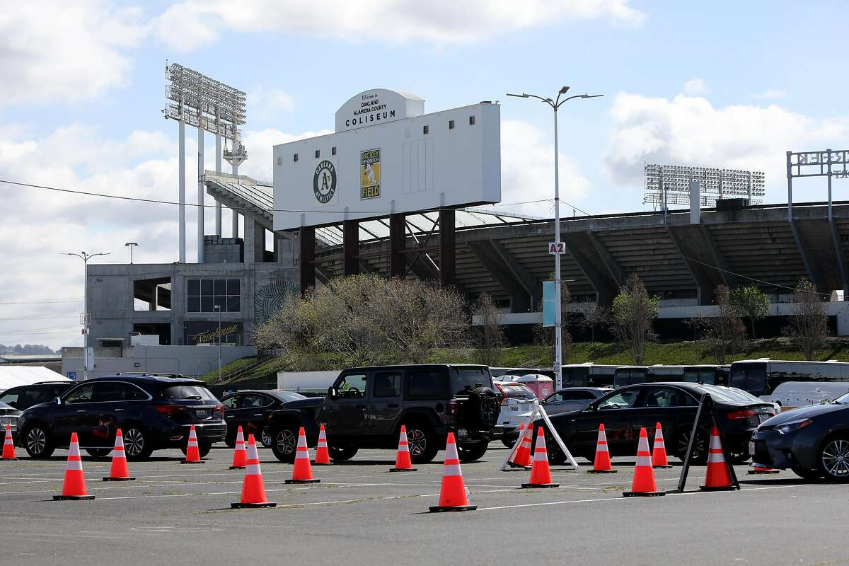 Vehicles wait in line at the Oakland Coliseum vaccination site on March 25, 2021.