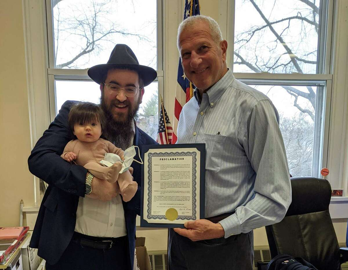 Mayor Mark Lauretti proclaimed March 24 Education and Sharing Day in Shelton. Lauretti celebrates the proclamation in his office with Rabbi Shneur Brook and his daughter, Dusya.